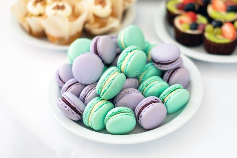 绿松石和紫罗兰色macarons 在桌上的婚宴喜饼 甜的点心 选择聚焦 库存照片