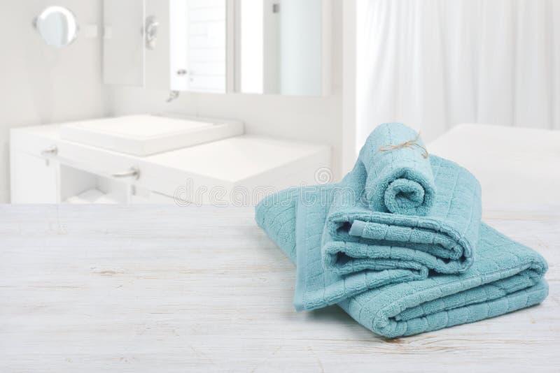 绿松石木表面上的温泉毛巾在被弄脏的卫生间背景 免版税库存图片
