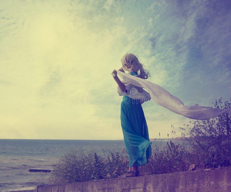 绿松石礼服的孤独的妇女有挥动的围巾的 免版税库存照片