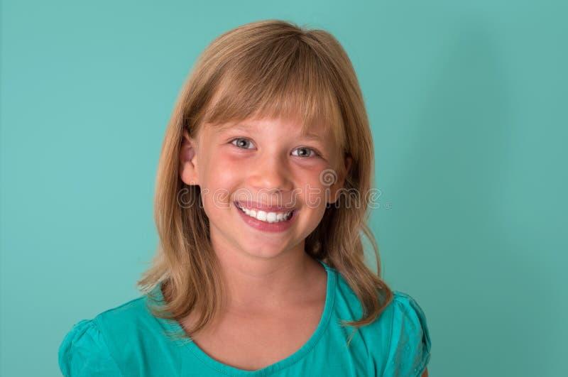 绿松石背景的愉快的微笑的小女孩a 情感 免版税库存图片