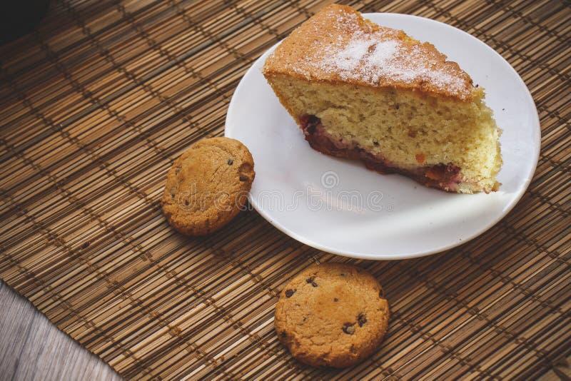 松糕片断在一块圆的白色板材的有巧克力bis的 库存图片