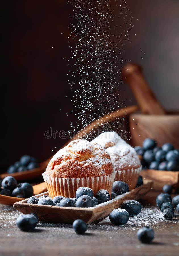 松饼和蓝莓洒与糖粉 免版税库存图片