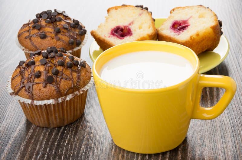松饼片断与充塞的,杯子用在桌上的牛奶 图库摄影