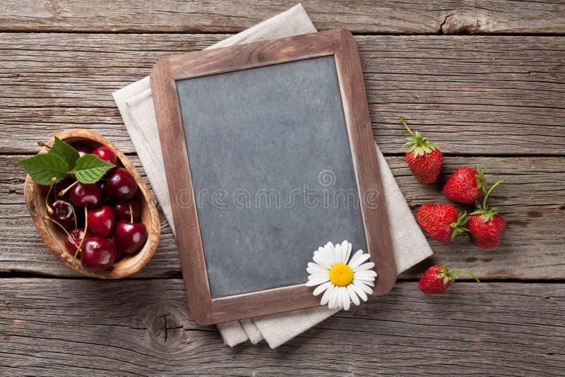 黑板和莓果 免版税库存照片