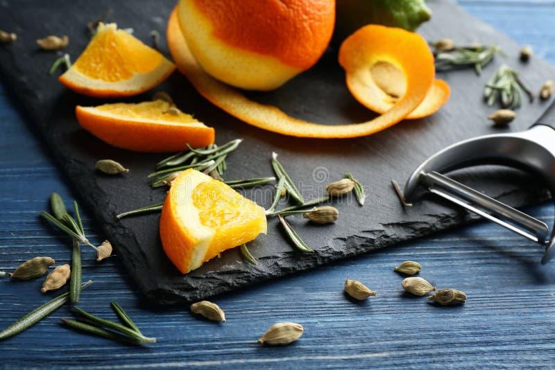 板岩板材用在木桌上的成熟柑桔 免版税库存照片