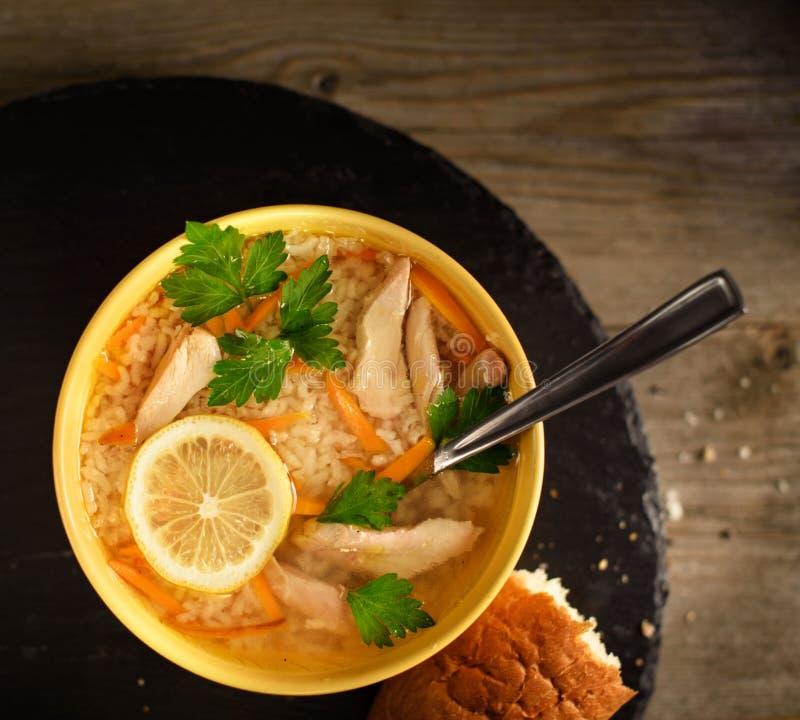 板材有汤顶视图 与鸡的米汤在一个黄色杯子,在面包片旁边 免版税图库摄影