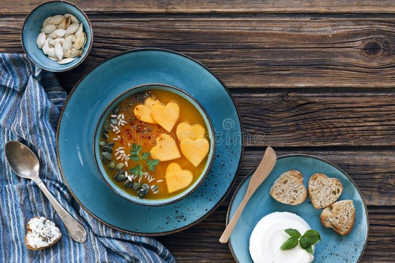 板材特写镜头照片用与种子的新鲜的自创南瓜奶油汤和心脏塑造在葡萄酒木背景的多士 库存照片