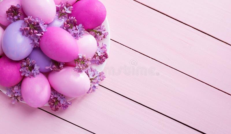 板材用丁香复活节彩蛋和花在一张桃红色木桌上的 顶视图 免版税库存照片