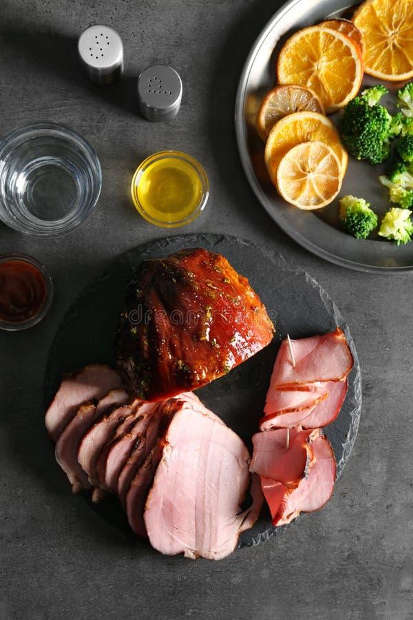 板材用切的蜂蜜烘烤了火腿和菜在桌上 免版税库存照片