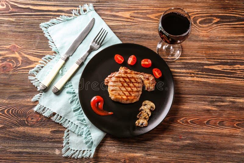 板材用可口烤牛排和杯在桌上的红酒 免版税库存照片