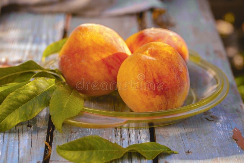 板材用在桌上的新鲜的甜成熟桃子 免版税库存图片