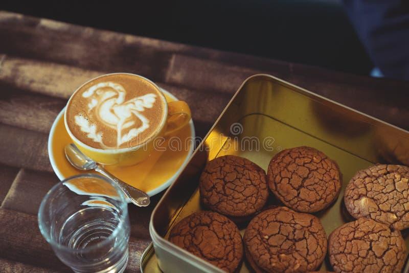 板材用巧克力曲奇饼和杯子在老木桌上的热的咖啡 顶视图 库存图片