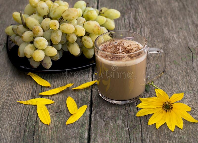 板材用葡萄、热奶咖啡、一朵黄色花和黄色peta 库存照片