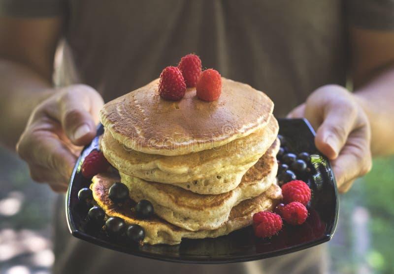 板材用蓬松鲜美薄煎饼和莓果在手上 免版税库存图片