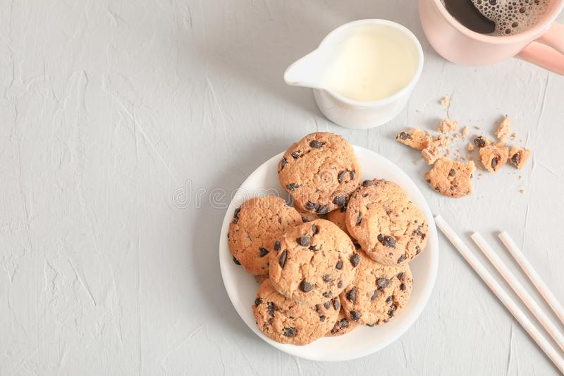 板材用鲜美巧克力曲奇饼和咖啡在灰色背景,顶视图的 免版税库存图片