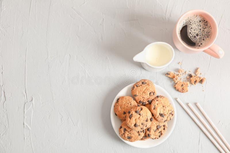 板材用鲜美巧克力曲奇饼和咖啡在灰色背景,顶视图的 库存照片