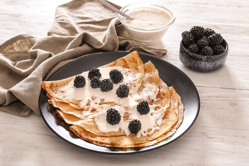 板材用鲜美稀薄的薄煎饼、莓果和酸性稀奶油在木桌上 图库摄影