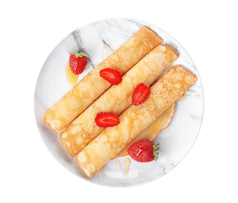 板材用鲜美稀薄的薄煎饼和新鲜的莓果在白色背景 免版税库存照片