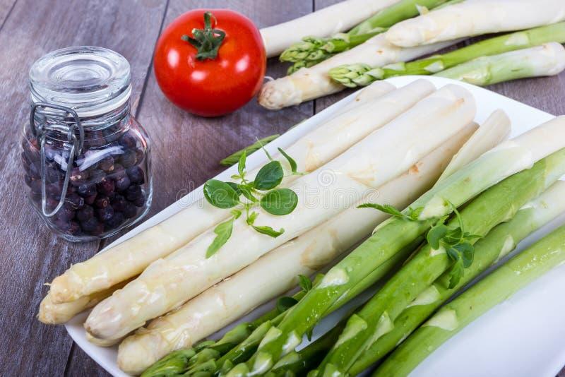 板材用绿色和白色芦笋、香料和蕃茄 免版税图库摄影