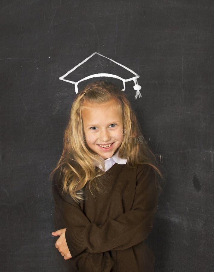 黑板的甜女小学生有有白垩略图的毕业帽子微笑愉快 库存照片