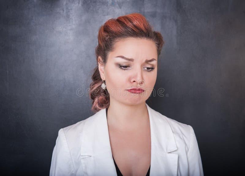 黑板背景的哀伤的妇女 库存图片
