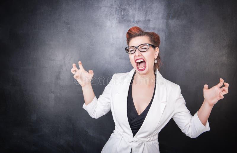 黑板背景的疯狂的叫喊的老师 库存图片