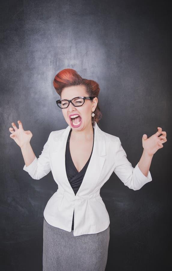 黑板背景的疯狂的叫喊的老师 免版税库存照片
