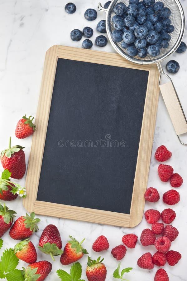 黑板黑板莓果标志背景 免版税库存照片
