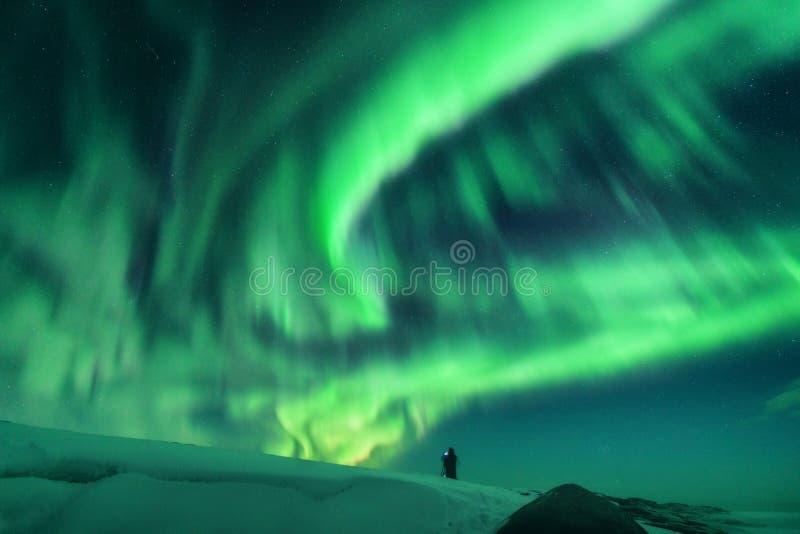 极光一个人的borealis和剪影小山的 免版税库存照片