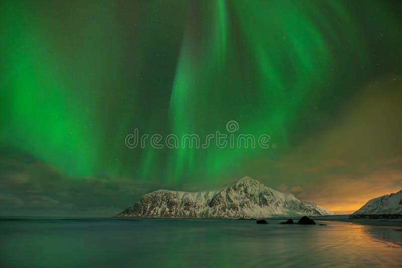 极光在山的borealis跳舞在雷讷和Sakrisoy的,罗弗敦群岛,访问罗弗敦群岛海岛的挪威渔村 库存图片