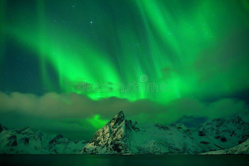 极光在山的borealis跳舞在雷讷和Sakrisoy的,罗弗敦群岛,访问罗弗敦群岛海岛的挪威渔村 免版税库存图片