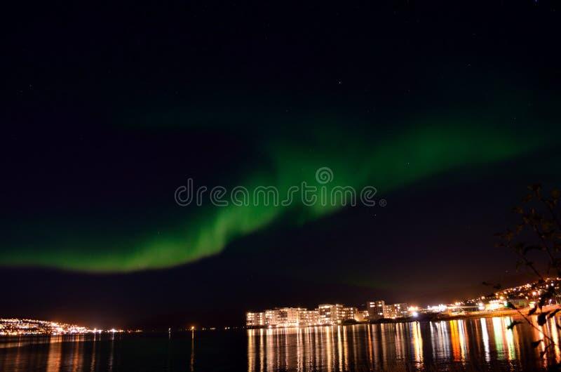 极光borealis和城市光反射在海湾浮出水面 库存照片