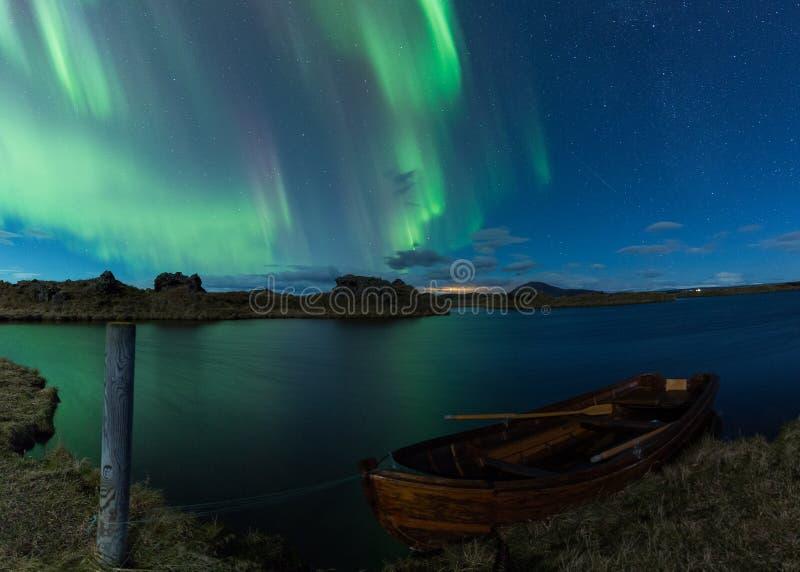 极光borealis在一个湖上的冰岛有小船的 库存照片