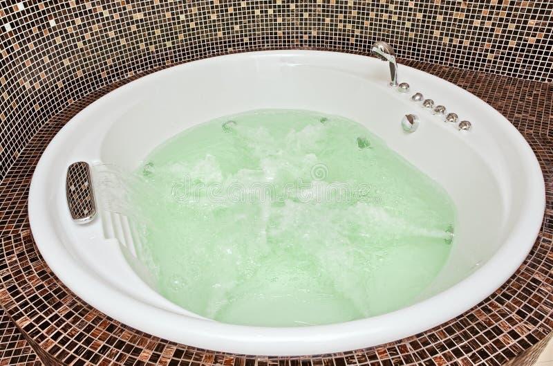 极可意浴缸马赛克打旋的水 库存照片