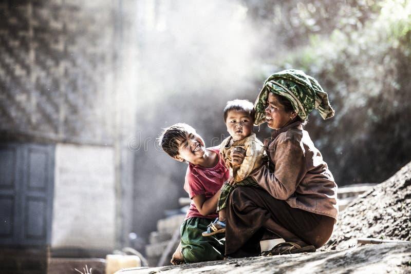 极小的南星期四村庄,蒲甘,曼德勒,缅甸- 2016年1月17日:从极小的南星期四村庄身分的孩子t的房子外 图库摄影