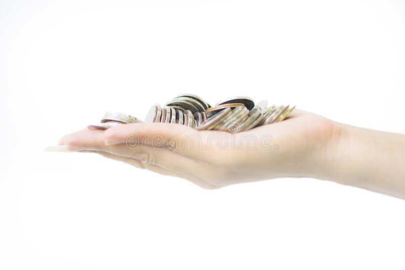 极少数硬币在妇女的棕榈手上在白色背景中 库存图片