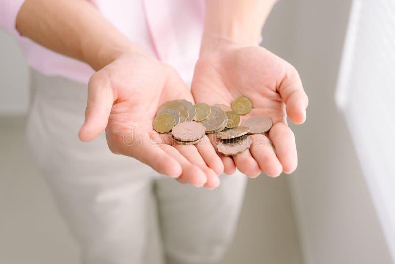 极少数硬币在棕榈男性手上 库存图片