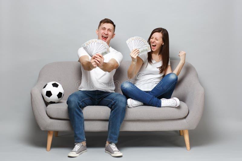 极度高兴的夫妇妇女人足球迷欢呼金钱支持喜爱的队藏品爱好者在美元钞票现金的 免版税库存照片