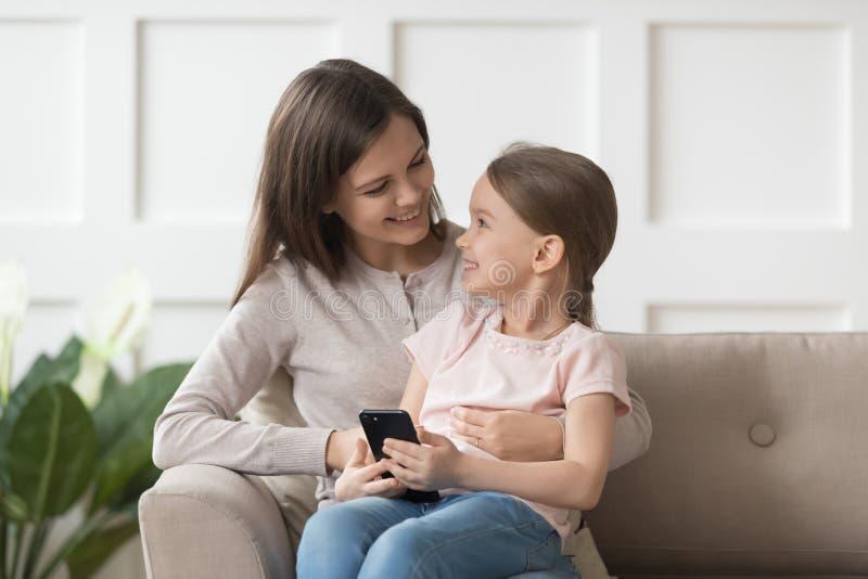 极度高兴的女儿藏品智能手机坐母亲舔 免版税库存图片