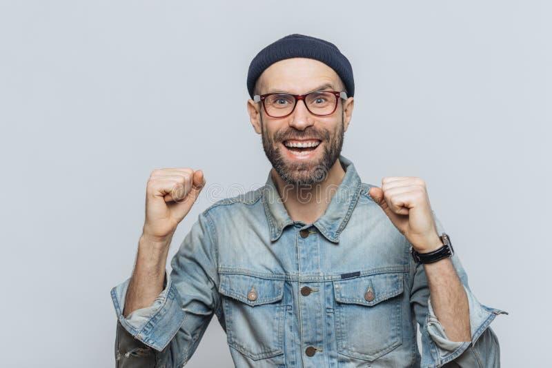极度高兴的男性高兴他的成功,紧握拳头,看joyfu 库存图片