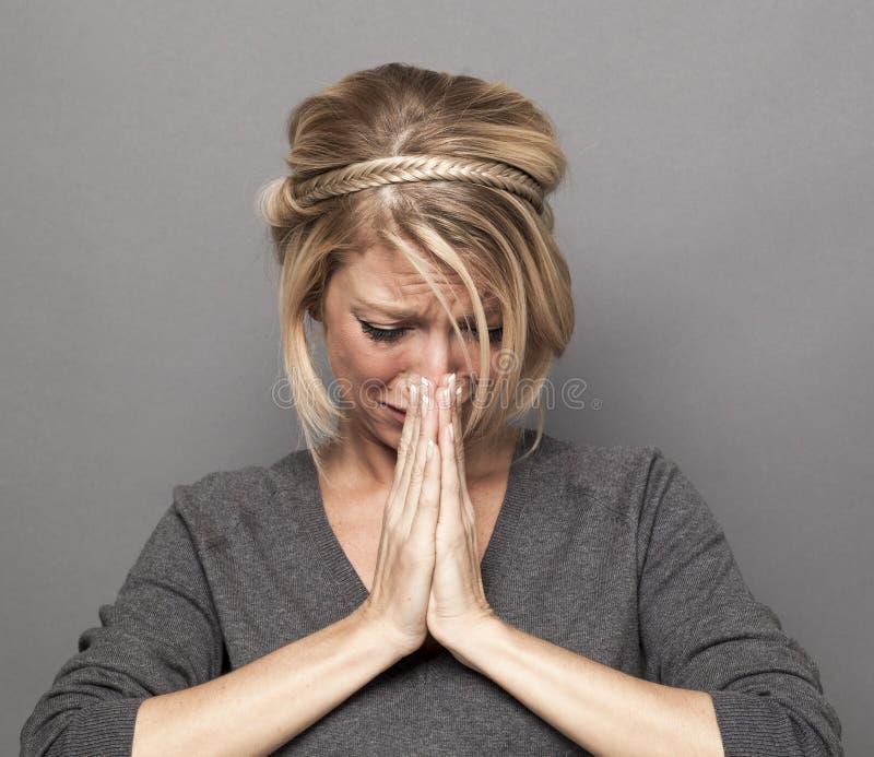 极悲痛的年轻白肤金发的妇女的祈祷的概念 库存照片