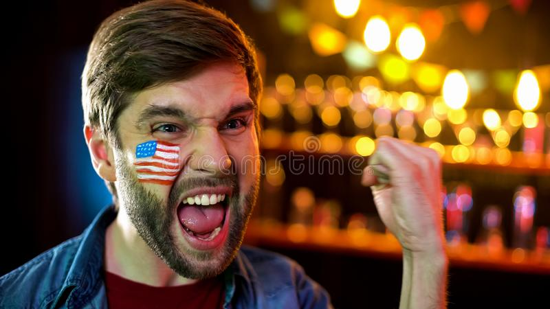 极端与旗子的愉快的美国足球迷在是做姿态,胜利的面颊 免版税库存照片