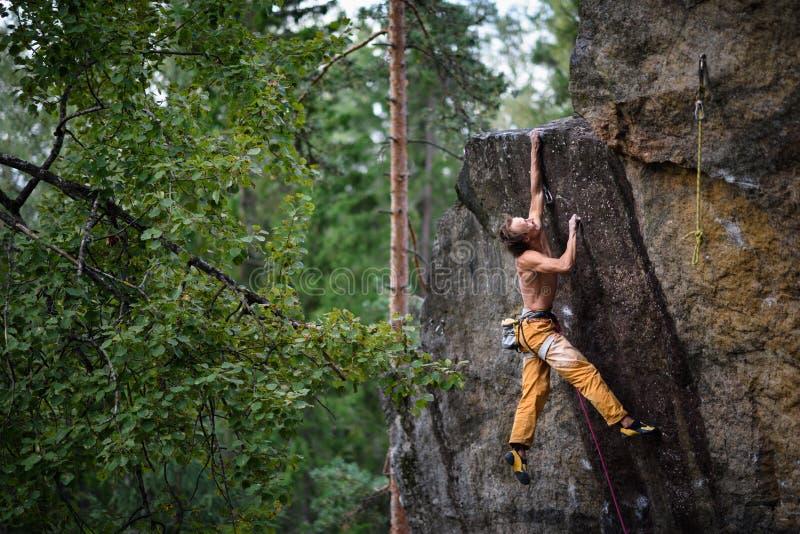 极端体育上升 到达岩石的上面的年轻男性攀岩运动员 库存图片