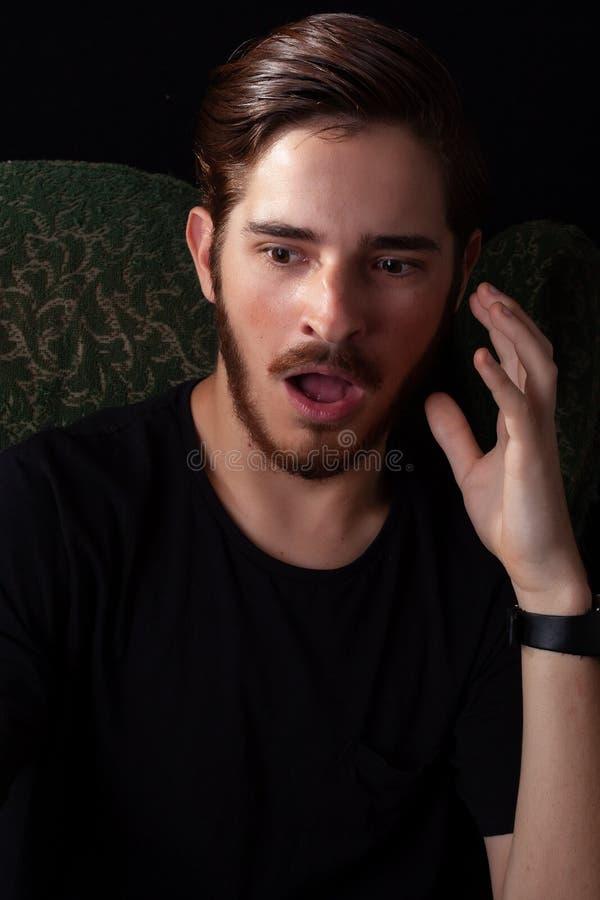 极端关闭看左边,对面颊嘴的手的年轻成年男性开放在震动 剧烈的作用的深刻的颜色口气,黑暗 图库摄影