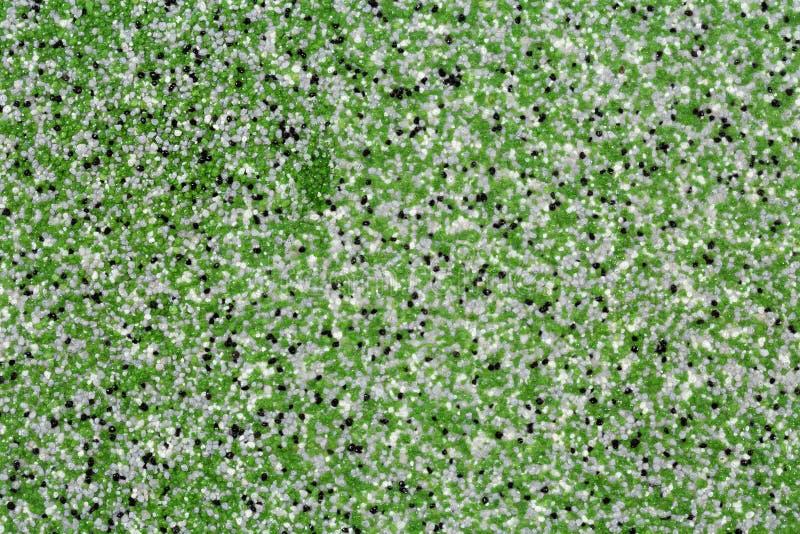 极端关闭装饰与绿色,灰色,白色和黑色的微粒的石英沙子环氧地板或墙壁涂层 免版税库存照片