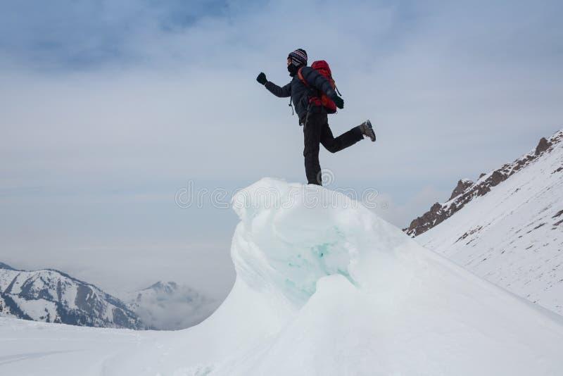 极端冬季体育:登山人在阿尔卑斯到达多雪的山峰的上面 概念:决心,成功,力量 库存照片