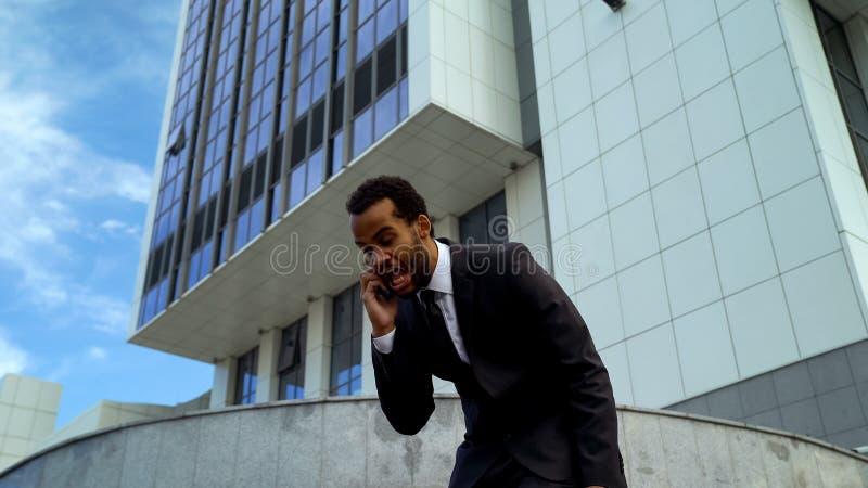 极端懊恼混血儿商人呼喊在电话的,劳累过度的雇员 免版税库存图片