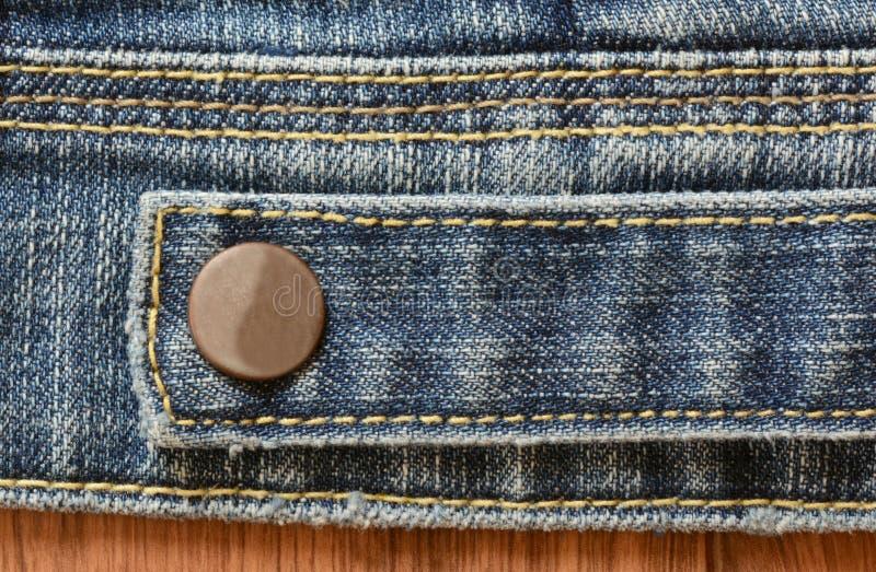 极端接近与固定的按钮的蓝色牛仔布纹理 库存照片