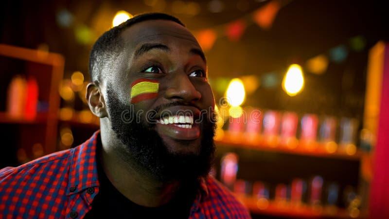 极端有旗子的呼喊愉快的黑人西班牙的爱好者在面颊,队赢得 库存照片