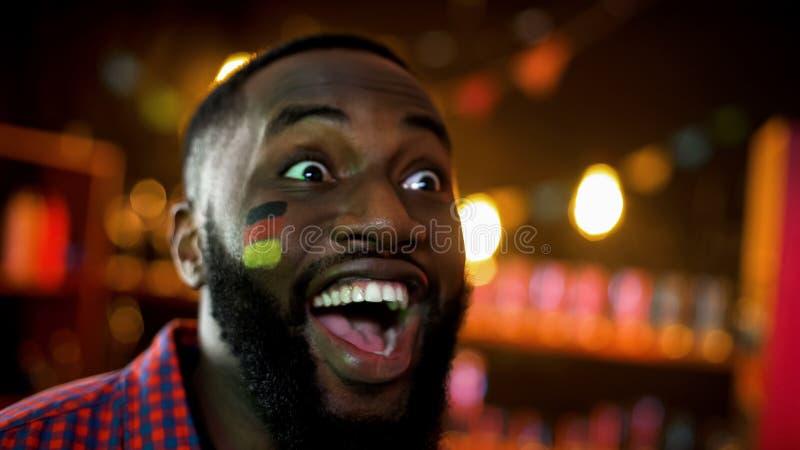 极端有旗子的愉快的黑人德国足球迷在面颊庆祝胜利的 免版税图库摄影